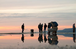 TRIESTE ITALIEN - FEBRUARI, 25, 2016: Fotoet med reflexion som en fotograf tar bilder 4 fiskare på solnedgång med moln, 1 M Arkivfoto