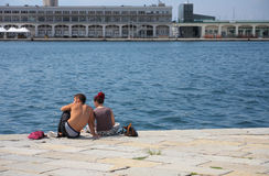 TRIESTE, ITALY - AUGUST 18, 2015: Young couple seats on Molo Aud Stock Photos