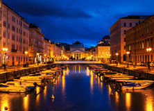 Trieste, Italy Canale Grande at night. Trieste, Italy. Church of St. Antonio Thaumaturgo with Canale Grande at night. Sunset sky with boats and illuminated stock image