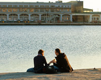 Trieste Italy - harbor, couple relax sitting on Molo Audace pier Stock Photos