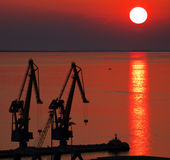 Trieste, Italy - old harbor, crane silhouettes at sunset Stock Images