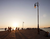 Trieste, Italy - people stroll along Molo Audace pier at sunset Royalty Free Stock Images