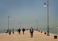 Trieste, Italy - people walk on Molo Audace sea promenade Royalty Free Stock Image