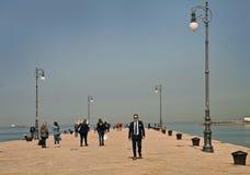 Trieste, Italy - people walk on Molo Audace sea promenade Royalty Free Stock Image