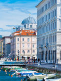 Trieste - Jule 2016, Italy: View of Grand Canal (Canal Grande) with boats on water and Serbian Orthodox Church Stock Photos