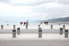Trieste, September 5 2017, Italy: traffic island and some people walking on a stone pier. Trieste, September 5 2017, Italy: traffic island and some people Royalty Free Stock Image