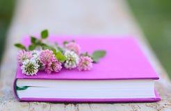 Trifoglio bianco rosa e sul libro fucsia Immagini Stock