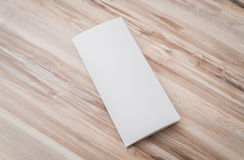 Trifold white template paper on wood texture . royalty free stock photos