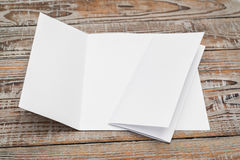 Trifold white template paper on wood texture . royalty free stock images