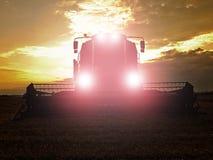 Trigo abandonado de la cosecha de la cosechadora con las luces principales encendidas en el medio de un campo de granja Campo de  Fotografía de archivo libre de regalías