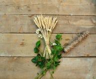 Trigo, corda e margaridas em um fundo de madeira Fotografia de Stock Royalty Free