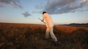Trigo de cosecha del campesino con una guadaña almacen de video