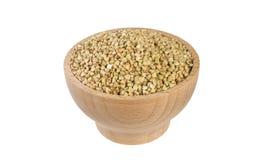 Trigo mourisco cru na bacia de madeira isolada no fundo branco nutrition Ingrediente de alimento imagens de stock royalty free