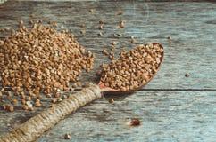 Trigo mourisco dispersado e uma colher completamente do trigo mourisco Imagem de Stock