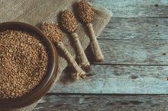Trigo mourisco em uma bacia de madeira e em uma colher completamente do trigo mourisco no fundo de madeira Fotos de Stock