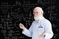Trigonometry class. Senior male teacher explaining trigonometry at the blackboard Stock Image