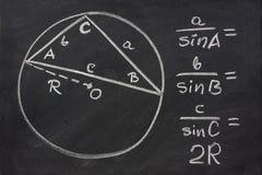 Trigonometry law explained on blackboard. Trigonometry identity - law of sines sketched with white chalk on blackboard, eraser smudges Stock Image