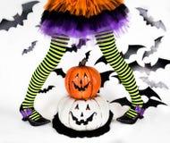 Trik eller fest Halloween ungar Randiga ben av lite häxaflickan med lyckliga smileypumpor Royaltyfri Fotografi
