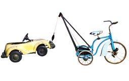 Trike mit einem Spielzeug-Auto im Schleppseil lizenzfreie stockfotos