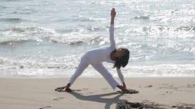 Trikonasana. Mature woman practicing yoga at the beach stock video