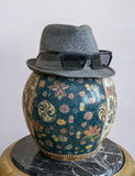 Trilby hat wearing sunglasses over antique decorated Chinese ceramic vase. Gray trilby hat wearing sunglasses over antique decorated Chinese ceramic jar vase Stock Photo