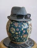 Trilbyhoed die zonnebril over antiquiteit verfraaide Chinese ceramische vaas dragen stock foto