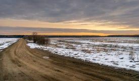 Trilha de sujeira longa através de um campo da neve Céu crepuscular fotos de stock royalty free