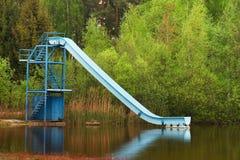 Trilha deslizante azul velha na praia do lago Foto de Stock Royalty Free