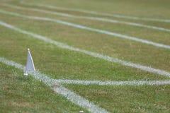 Trilha do atletismo da grama que mostra o marcador da bandeira branca Fotos de Stock Royalty Free