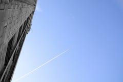 Trilha do avião no céu e na construção fotos de stock