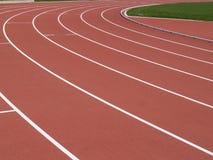 Trilha sintética do atletismo - vermelho fotos de stock royalty free