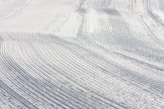 Trilhas da neve na inclinação feita por Ratrack Imagens de Stock