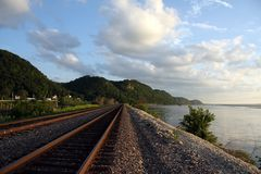 Trilhas de estrada de ferro pelo rio Fotografia de Stock Royalty Free