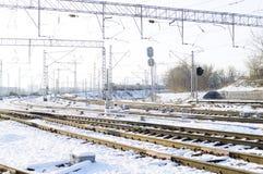 Trilhas de estrada de ferro na neve Vagões de estrada de ferro da mercadoria, inverno Fios de alta tensão acima das trilhas de es fotos de stock royalty free