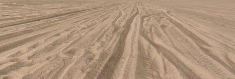 Trilhas do pneu através da areia do deserto Fotos de Stock Royalty Free