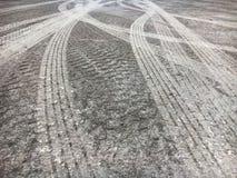 Trilhas do pneu na estrada áspera do cimento imagem de stock royalty free
