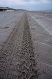 Trilhas do pneu na praia Imagem de Stock