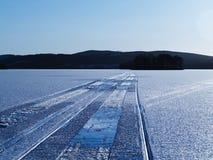 Trilhas do Snowmobile no lago Imagens de Stock Royalty Free