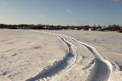 Trilhas do trator no campo do inverno Fotografia de Stock