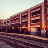 Trilhas do trem por uma construção do estacionamento Fotografia de Stock Royalty Free