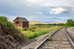 Trilhas velhas da casa e de estrada de ferro Fotografia de Stock