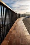 Trilhos metálicos e de madeira em um penhasco da costa iluminado pela luz do por do sol fotografia de stock