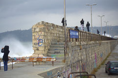 Trill seekers looking waves flooding breakwater. Huge waves flooded Varna breakwater walking people and cars on the street to marine station, the port is closed Royalty Free Stock Images