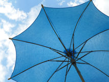Trillend blauw gekleurd zonnescherm tegen heldere blauwe hemel en witte wolk Stock Afbeelding