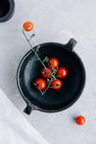 Trillend Cherry Tomatoes op de Wijnstok in Donker Clay Rustic Pot op Grey Kitchen Worktop Stock Foto