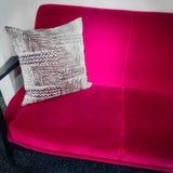 Trillende roze fluweelbank met sierkussen Stock Foto's