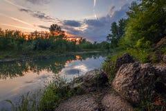 Trillende zonsondergangscène dichtbij een vijver met rotsen in de voorgrond stock foto's