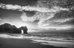Trillende zonsopgang over oceaan met rotsstapel in voorgrond in blac Stock Afbeeldingen