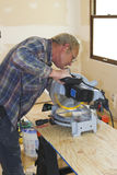 Trim carpenter. Cutting trim for window casing in home the is being restored Royalty Free Stock Photo