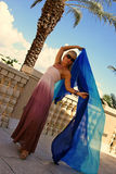 Trim woman holding blue veil. Long slender female on balcony in dress and sunglasses holding blue silk cloth Stock Photo
